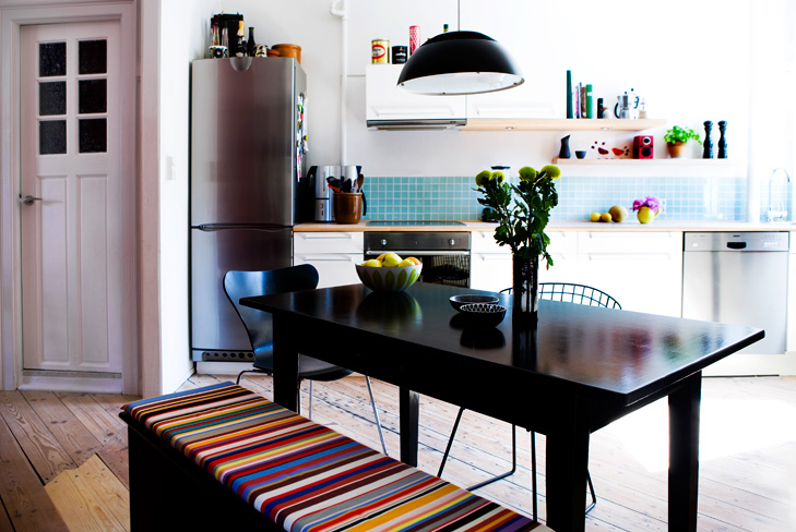 Indretning af køkken og spiseplads i samtale køkken. Spisebord med blomster på