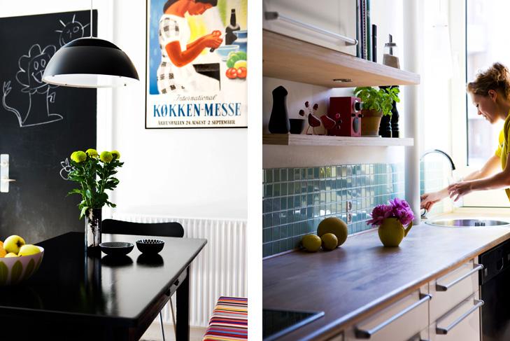 Indretning af køkken med spisebord og plakat i baggrunden samt køkkenbord med glasfliser, blomster og køkkenvask