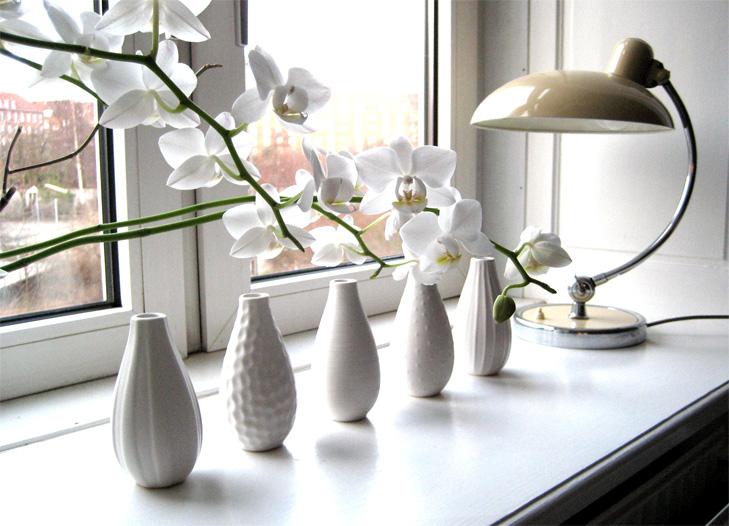 Detalje af vindueskarm med lampe, blomster og vaser