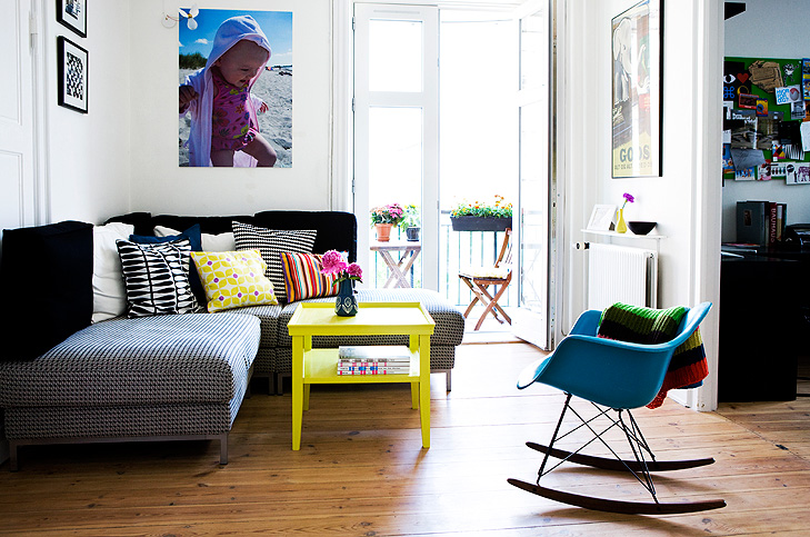 Interior decoation of small living room with a sofa, a yellow sofa table and a large poster with a kid