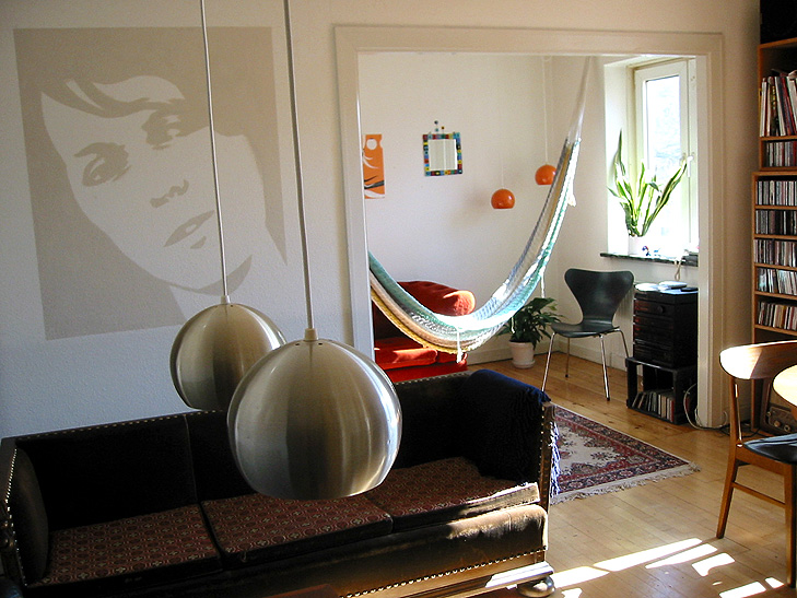 Indretning af stue i retro stil med hængekøje, vægmaleri og antik kistesofa