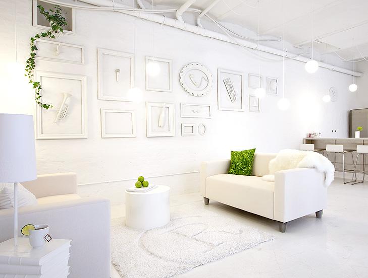 Indretning af lounge på kontor med hvide sofaer og et hvidt tæppe. På væggen hænger hvidmalede rammer med hvide 3d objekter i.