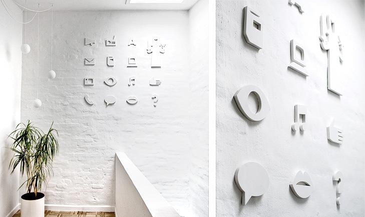 Billeder af vægrelief fra indretning. Relieffet forestiller en række ikoner med afsæt i teamet kommunikation.