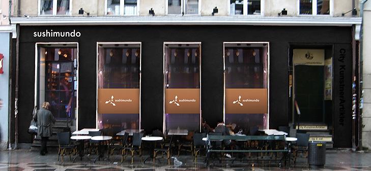 Facadefoto af restauranten Sushimundo med kobberskiltning og lilla belysning i vinduerne.