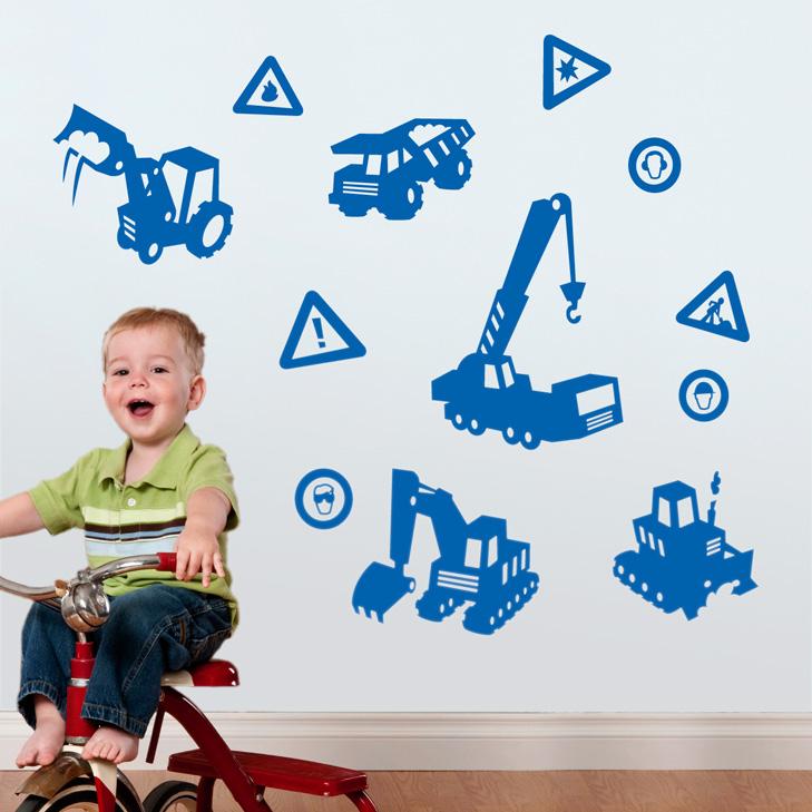 Dreng på 3 hjulet cykel i forgrunden. På væggen hænger blå wallstickers i silhouet med forskellige maskiner fra byggeplads. En dumper, en gravko, en kran og en bulldozer samt forskellige advarselsskilte.