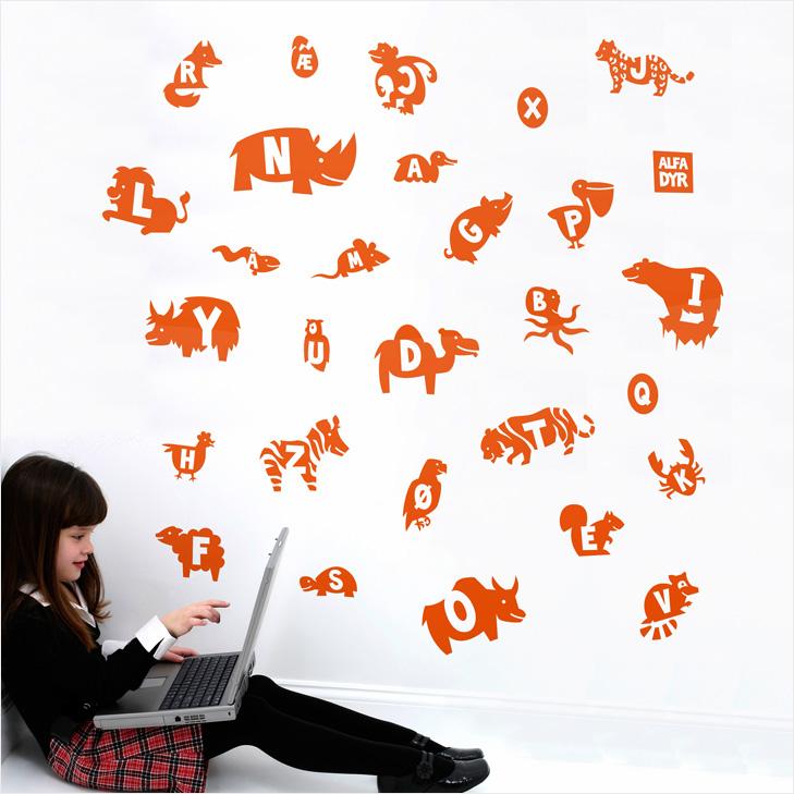 Pige sidder med laptop ved siden af væg med orange wallstickers der forestiller forskellige dyr. Dyrene har deres forbogstav skrevet inde i sig.