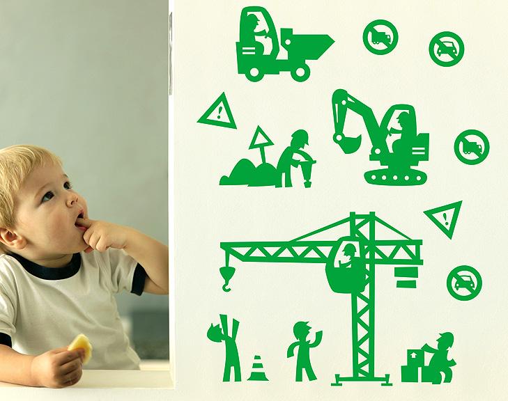 Dreng sidder og spiser et udskåret æble ved siden af en væg med grønne wallstickers. Motiverne er tegnet i silhouet i tegneseriestil. Der er en lille dumper, en mand der sidder i en kran, en mand der råber til kranføreren, en mand der sidder på nogle kasser, en mand der bruger et trykluftbor.