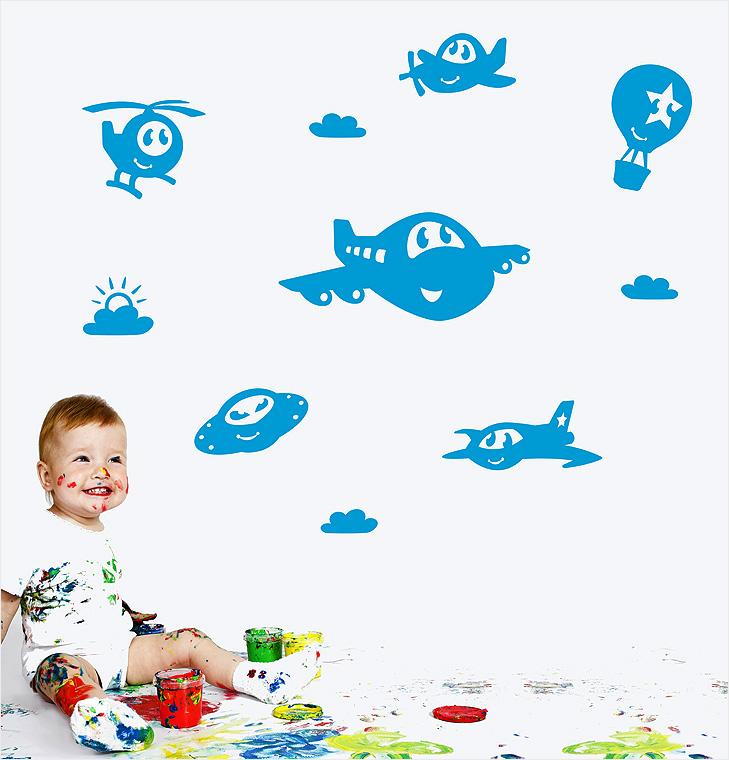 En baby der leger med maling sidder foran en hvid væg med med blå wallstickers der foretiller forskellige flyvemaskiner som har øjne og mund. De smiler. Bland andet en jumbojet, en helikopter, en luftballon, et propelfly, en ufo og en sky.