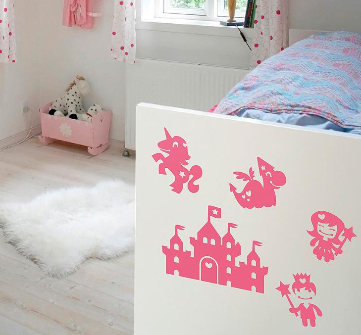 Billede af bagenden af en seng på et pigeværelse. Sengen har påklistret lyserøde wallstickers tegnet i silhouet som forestiller, prinsesser, eventyrslotte, troldmænd og unicorns.