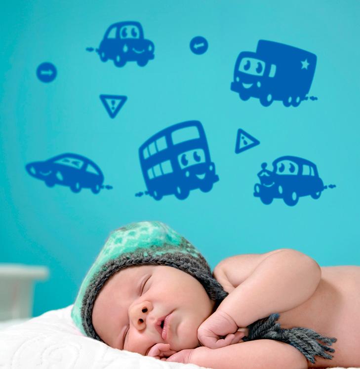 Baby med hue ligger i forgrunden. Bag babyen er en turkis væg med blå wallstickers i silhouet med søde motiver af køretøjer med øjne og mund. De smiler. Der er en dobbeltdækker bus, en sportsvogn, en personbil, en veteranbil og en lastbil.
