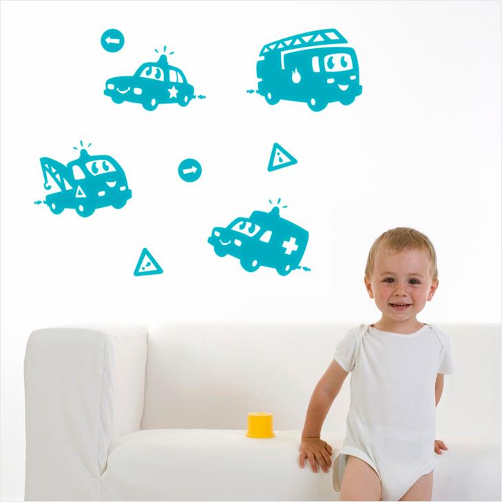 Baby står foran hvid sofa i body. På væggen bag babyen hænger nogle turkise wallstickers som forestiller udrykningskøretøjer i silhouet med øjne og mund. Der er en politibil, en brandbil, en ambulance og en kranvogn.