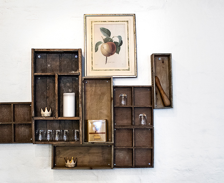 Interior decoration with shelving made of old wooden boxes. On the top of the shelves there is a frame with an old nature drawing of a peach.
