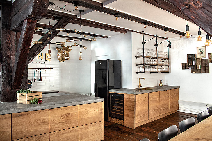Overview of the interiors in a show kitchen constructed of raw oak wood, rough concrete table tops and with big wooden beams and pillars in dark rough wood.