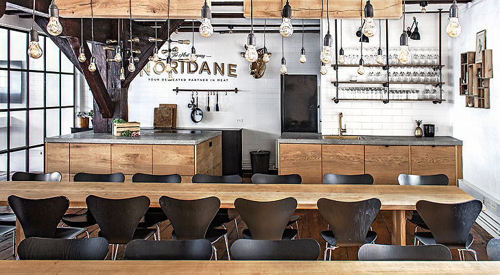 Overview of the interiors of a canteen med massive raw oak wood tables and balck wooden chairs. In the ceiling there is hagning some decorative oak beams with light bulps in black wires.