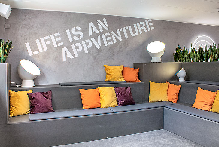 Photo of a custom designed furniture built in MDF. The lounge furniture has terraces for seating and has 3 levels. The floor has a grey carpet and the wall has a grey concrete look. Orange, purple and yellow cushion are lying on the seatings and to the right there is a white neon sign with the company logo.
