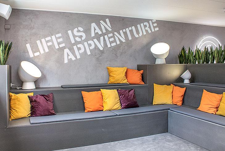 Billede af lounge indretning specialbygget i grå MDF. Lounge møblet er en række små terrasser der strækker sig over 3 niveauer. På gulvet ligger et gråt gulvtæppe. Bagvæggen er pudset op med et gråt beton look og der ligger orange, gule og lilla puder spredt på lounge møblet. Bagerst ses et hvidt neon skilt med firmaets logo.
