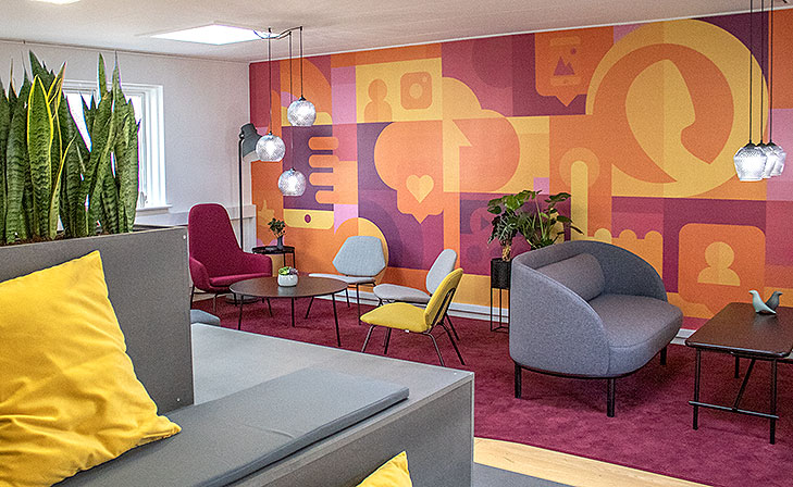 Lounge interior design seen from the right. In the foreground there is a customized lounge furniture with terraces, a yellow cushion and built in fower pots. Behind it there is a big purple carpet. To the right there is two Fuuga sofas with black legs and a Peter Boy sofa table. To the left there is a round black lounge table, yellow lounge chairs from Woud and purple armchairs from Normann Copenhagen. On the wall behind gthe lounge there is a big floor to ceiling wall painting in yellow, orange and purple colors. The wallpainting is abstract with recognisable elements like a cellphone, social media icons, communicatuon and app development. Both sofa tables have glas pendant lamps with crystal patterns hanging over them.