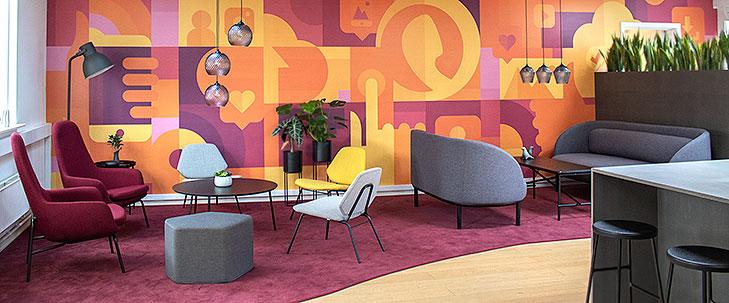 Lounge indretning set fra venstre side. I forgrunden ses et specialbygget terrasse bar bord i gråt MDF med sorte barstole i sort træ og med tynde sorte stålben. Bagved ses et stort bordeaux farvet gulvtæppe. Til højre er der et sofa arrangement med to grå Fuuga sofaer med sorte ben og et sort Peter Boy sofa bord. Til venstre er der et rund sort lounge bord med grå og gule lounge stole fra Woud og lilla lænestole fra Normann Copenhagen. På væggen bag loungen ses et gulv til loft vægmaleri med store farveflader i gule, orange og lilla nuancer. Vægmaleriet er abstrakt med enkelte genkendelige elementer som mobiltelefoner, ikoner fra sociale medier, telekommunikation og app udvikling. Over begge sofaborde hænger pendler i glas med krystal-slebet mønster. I baggrunden til højre ses en specialbygget høj blomsterkasse.