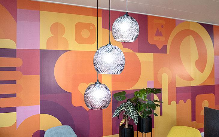 Nærbillede af lounge indretning. I forgrunden ses 3 glaspendler med krystal-slebet mønster. På væggen i baggrunden ses et På væggen bag loungen ses et gulv til loft vægmaleri med store farveflader i gule, orange og lilla nuancer. Vægmaleriet er abstrakt med enkelte genkendelige elementer som mobiltelefoner, ikoner fra sociale medier, telekommunikation og app udvikling. Op mod væggen står der to potteplanter.