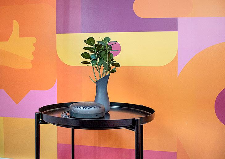 Nærbillede af et sort sidebord fra loungeindretning med lille potteplante og B&O Play højtaler. I baggrunden ses et gulv til loft vægmaleri i gule, orange og lilla nuancer.