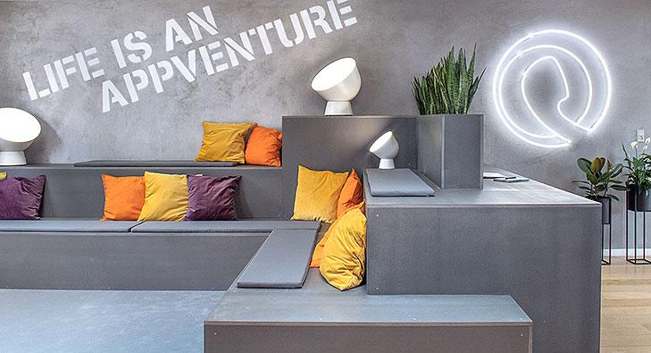 Billede af lounge indretning med et specialbygget møbel i grå MDF. Møblet er et siddemøbel med 3 terrasse nuveauer. Der ligger ryg- og siddepuder på niveauerne og der står hvide gulvlamper på nogle sæder. På den grå beton væg står der Life Is An Appventure med stencil skrift. Til højre på væggen hænger der et hvidt neon skilt med firmaets logo.